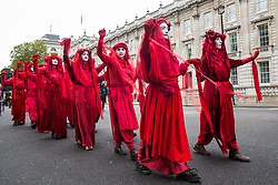 London, UK. 7 October, 2019. Red Brigade climate activists from Extinction Rebellion march along Whitehall on the first day of International Rebellion protests to demand a government declaration of a climate and ecological emergency, a commitment to halting biodiversity loss and net zero carbon emissions by 2025 and for the government to create and be led by the decisions of a Citizens' Assembly on climate and ecological justice.