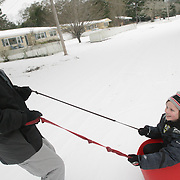 Mark Olsen, left, pulls Caleb Knight-Olsen,10, on Winston Blvd. in Wilmington, N.C. Wednesday January 29, 2014. Wilmington saw a wintry mix of sleet, snow, and freezing rain Tuesday and Wednesday which caused extensive closings throughout the area. (Jason A. Frizzelle)