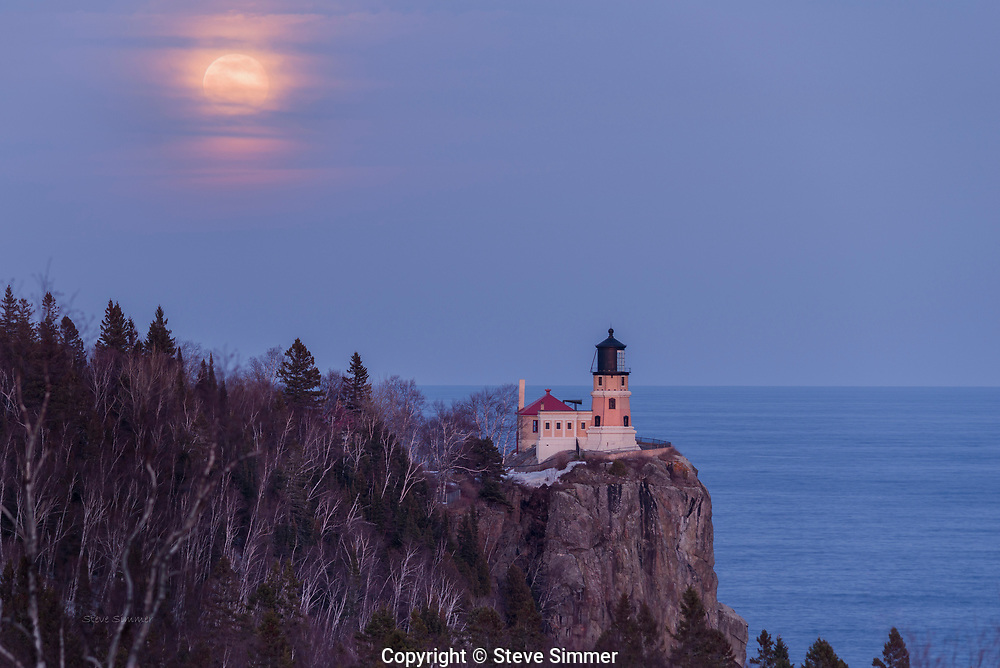 Twice a year a full moon rises near the lighthouse, as seen from the Hwy 61 overlook.  Often, clouds or fog obscure the view. This year the moon managed to push through light clouds and put on a show.