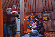 Grandfather Batjarjral Tulge plays with his granddaughter in the warmth of the interior of the family ger tent whilst grandmother Dolgormaa prepares the evening meal.