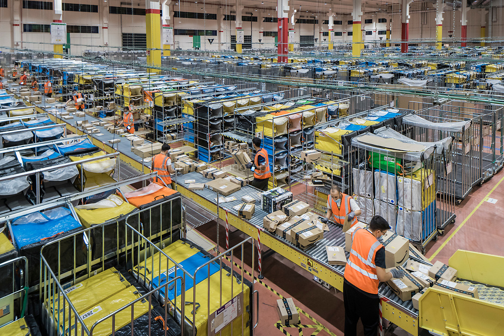 ARZANO, ITALY - 18 SEPTEMBER 2020: Diverters process Amazon packages at the Amazon delivery station in Arzano, just outside Naples, Italy, on September 18th 2020.<br /> <br /> Opened in 2019, the Amazon delivery station in Arzano was the first to open in Southern Italy. Here, an average of 30,000 to 50,000 Amazon packages are processed and delivered in the region.<br /> <br />    plans to open two new fulfillment centers and seven delivery stations. Roughly 1,600 more people will be hired by the end of the year, pushing its full-time work force in Italy to 8,500 from less than 200 in 2011. <br /> <br /> Amazon has been one of the biggest winners in the pandemic as people in its most established markets — the United States, Germany and Britain — have turned to it to buy everything from toilet paper to board games. What has been less noticed is that people in countries that had traditionally resisted the e-commerce giant are now also falling into Amazon's grasp .<br /> The shift has been particularly pronounced in Italy, which was one of the first countries hard hit by the virus. Italians have traditionally preferred to shop at local stores and pay cash. But after the government imposed Europe's first nationwide virus lockdown, Italians began shopping online in record numbers. <br /> 75 percent of Italians shopped online during the lockdown. In 2020, total online sales are estimated to grow 26 percent to a record 22.7 billion euros, according to researchers from Polytechnic University of Milan.
