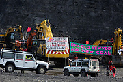Hundreds of environmental activists stopping the open cast coal mine Ffos-y-Fran near Merthyr Tydfil, Wales from operating May 3rd 2016. Unchallenged by security the activists enter the mine which is not in operation and empty for any other activity and set up banners and form a symbolic red line in the black sand. A couple of vehicles with employees make sure everyone are safe in the mine. The activists from Reclaim the Power wants the mine shut down and a moratorium on all future open coal mining in Wales. The group Reclaim the Power had set up camp near by and had over three days prepared the action and up to 300 activists all dressed in red went into the mine in the early morning. The activist were plit in three groups and carried various props signifying the red line in the sand, initially drawn in Paris at the COP21. The mine is one of the largest open cast coal mines in the UK and is run by Miller Argent who have to date extracted 5million tons of coal. The activists entered the mine unchallenged by any security or police and the protest went on peacefully till mid afternoon with no arrests made.  Open coal mining is hugely damaging to the local environment and  contributing to global climate change.