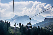 From Alleghe village, take a scenic lift to hikes on impressive Monte Civetta (3220 meters or 10,564 feet elevation) in the Dolomites, Belluno province, Veneto region, Italy. Marmolada, highest peak in the Dolomites, rises in the distance on the right. The Dolomites or Dolomiti are part of the Southern Limestone Alps in Europe. UNESCO honored the Dolomites as a natural World Heritage Site in 2009.
