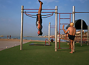 Two Spanish gentlemen exercise on the beach near Port Olympic in Barcelona, Spain.