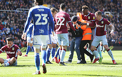 A fan is held is held after attacking Aston Villa's Jack Grealish (left)