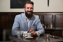 Portrait of smart man sitting by table with coffee cup and mobile phone on it at restaurant