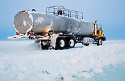 Alaska, North Slope. A water truck paves an ice road during construction.