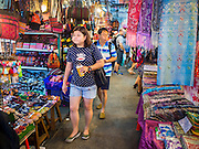 18 APRIL 2015 - BANGKOK, THAILAND:  Shoppers walk through Chatuchak Weekend Market in Bangkok. Chatuchak Weekend Market in Bangkok is reportedly the largest market in Thailand and the world's largest weekend market. Frequently called J.J., it covers more than 35 acres and contains upwards of 5,000 stalls.       PHOTO BY JACK KURTZ