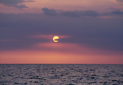 The sun behind purple clouds at sunset over the ocean