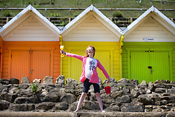 © Licensed to London News Pictures. 05/06/2016. Scarborough UK. 10 year old Cerys stand's in front of the beach huts at Scarborough beach on another sunny day in Yorkshire. Photo credit: Andrew McCaren/LNP