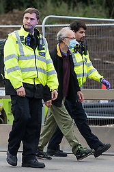 Enfield, UK. 15th September, 2021. Metropolitan Police officers arrest an Insulate Britain climate activist who had blocked a slip road from the M25 at Junction 25 as part of a campaign intended to push the UK government to make significant legislative change to start lowering emissions. The activists, who wrote to Prime Minister Boris Johnson on 13th August, are demanding that the government immediately promises both to fully fund and ensure the insulation of all social housing in Britain by 2025 and to produce within four months a legally binding national plan to fully fund and ensure the full low-energy and low-carbon whole-house retrofit, with no externalised costs, of all homes in Britain by 2030 as part of a just transition to full decarbonisation of all parts of society and the economy.