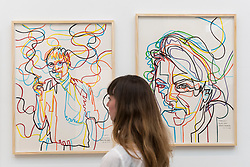 "© Licensed to London News Pictures. 17/05/2019. LONDON, UK. A woman views ""David (Hockney)"" (L), 2019, and ""Tracey (Emin)"", 2019, both by Gérard Fromanger at the Draw Art Fair London, the first fair in the UK dedicated to modern and contemporary drawing.  58 international galleries have juxtaposed drawings with related paintings, sculptures, photos or videos, in a ratio of approximately 70% to 30%, using drawing as the core concept.  The inaugural show is open to the public 17 to 19 May 2019 at the Saatchi Gallery in Chelsea.  Photo credit: Stephen Chung/LNP"