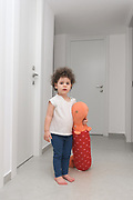 Toddler plays indoors with a large doll