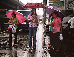Former Overseas Filipino Workers, OFWs, now working with Development Action for Women Network, DAWN, an aid organization aimed at providing skills for Filipino women who worked for Japanese clients and their Japanese-Filipino children, wait for the bus after working in a tailoring workshop in Manila, Philippines on Dec. 2006.  Many of the women employed by DAWN left the Philippines to work as entertainers in Japan. Several were later sexually abused, coerced into prostitution and now have children with Japanese fathers.