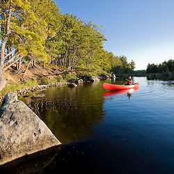 A man paddles his canoe on Seboeis Lake near Millinocket, Maine. (MR)