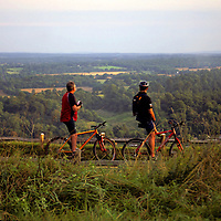 United Kingdom, Great Britain, England, London. Cyclists rest to appreciate a scenic vista of Box Hill, south of London in Surrey, preserved by the National Trust.