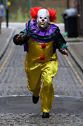 "POSED BY MODEL A person wearing a clown costume in a street in Liverpool. The ""killer clown"" craze has continued to spread across the UK with one force dealing with 14 reports in 24 hours."