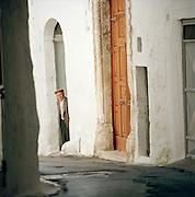 Older man in a doorway looking down a street in Ostuni, Puglia, Italy