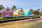 Pastel colored cottages along the water with coconut palms on Green Turtle Cay, Bahamas.