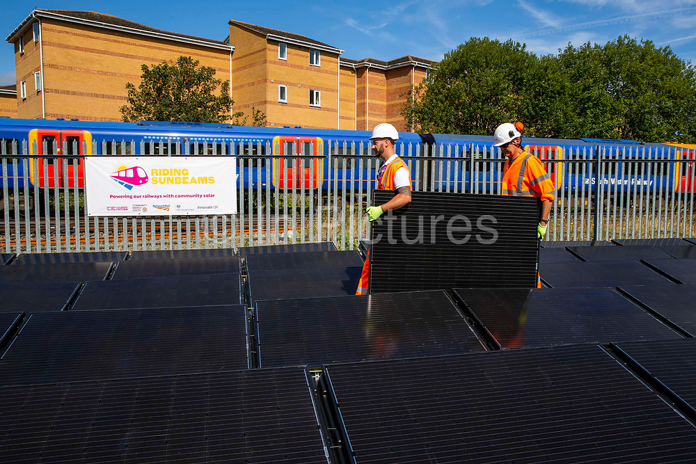 A train travels past an array of solar panels next to the line near Aldershot Railway Station on 23rd August 2019 in Aldershot, United Kingdom. This innovative project is the first in the UK to power the railway with electricity generated from solar power and, if successful, could see many Network Rail sites across the country adapting this sustainable energy approach. Riding Sunbeams is a social enterprise, run by 10:10 Climate Action. Built with Community Energy South and partnered with Network Rail and The Department for Transport and by InnovateUK.  Aldershot, Hampshire, United Kingdom. Riding Sunbeams is a world leading project to connect solar panels directly into electrified rail routes to power the trains. Direct supply of solar power to rail traction systems has never been done. But it has huge potential - from metros, trams and railways in the UK and around the world.