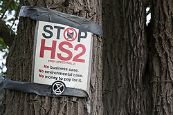 Harefield, UK. 27th April 2019. A sign placed by environmental activists from Colne Valley Action gathered to prevent the felling of trees as part of work scheduled for this weekend for the HS2 project. The Colne Valley is an area of natural beauty and large areas of trees have been felled there for HS2 in recent weeks. Protesters based at the Harvil Road Wildlife Protection Camp are seeking to prevent further destruction.