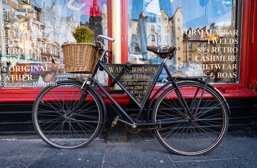 Bicycle outside W Armstrong & Son vintage clothes shop at Grassmarket in Edinburgh Old Town, Scotland, UK