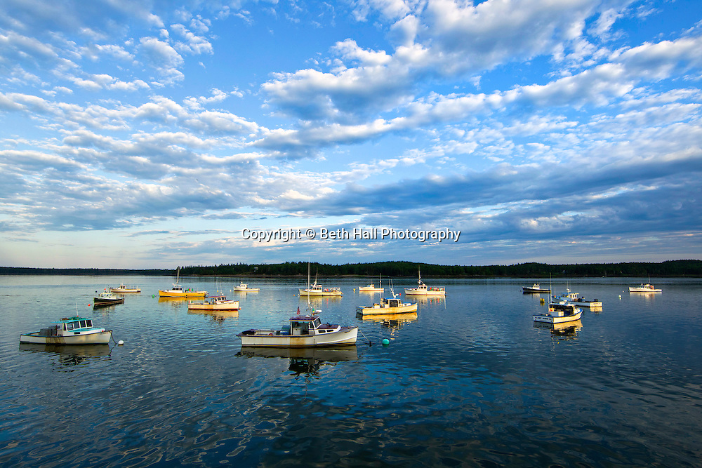 Lobster boats seen against a cloudy blue sky are lit by morning sunlight.