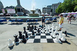 © Licensed to London News Pictures. 18/07/2021. LONDON, UK. Boys play chess on an outdoor chessboard at Chess Fest in Trafalgar Square.  The event celebrates the game of chess and visitors can learn the game, play chess or challenge a Grandmaster.  Also, to celebrate the 150th anniversary of Lewis Carroll's Alice Through the Looking Glass book which featured the game of the chess, 32 actors dressed as Alice Through the Looking Glass characters stand on a giant chessboard replaying a game based on the book.  Photo credit: Stephen Chung/LNP
