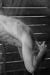 muscular man in an outdoor shower