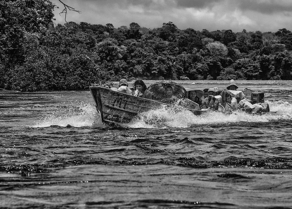 Fleuve Oyapock, Ilha Bela, 2015.<br /> <br /> Pirogue « clandestine » de garimpeiros à proximité d'Ilha Bela. Chaque matin, les pirogues partent d'Oiapoque pour ravitailler ce « village frontière », base arrière de l'orpaillage clandestin sur la rive brésilienne de l'Oyapock, à proximité de Camopi.<br /> <br /> La région connait depuis les années 1990 sa seconde ruée vers l'or. Dans un premier temps, le fleuve est exploité par des barges, des pompes sont installées sur des radeaux à la recherche de l'or alluvionnaire. Aujourd'hui, après l'épuisement des sables aurifères les garimpeiros s'intéressent aux anciens chantiers miniers guyanais. <br /> L'Oyapock est devenu un axe de transit de matériel, de ravitaillement et de main d'œuvre clandestine. La Camopi et la Sikini, deux affluents du fleuve, constituent les voies d'accès qui permettent de se rendre sur les chantiers de la région mais aussi de rejoindre les bassins du Maroni et de l'Approuague, principales zones aurifères de Guyane.