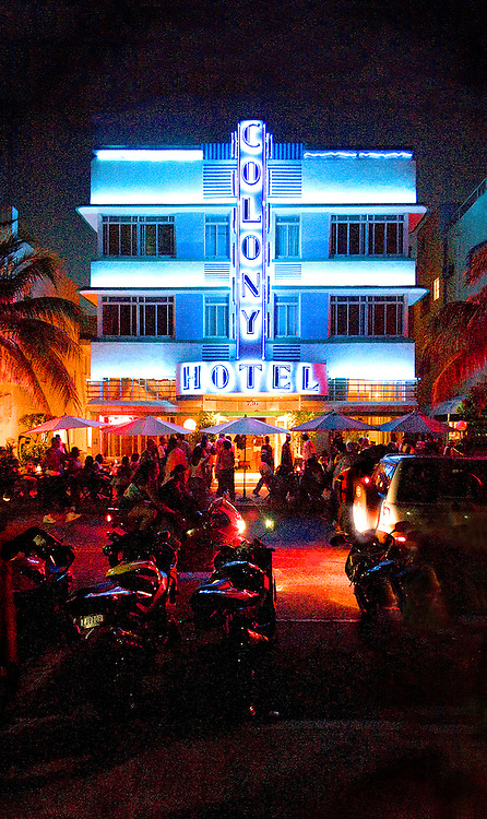 Night on Miami Beach's Ocean Drive in South Beach with motorcycles and the neon-lit, Art Deco style, Colony Hotel, designed by architect Henry Hohauser in 1935.