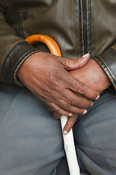 Visually-impaired person's hands with white stick at a resource for people with physical and sensory impairment.