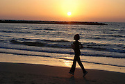 Israel, Tel Aviv, running on the beach at Sun set over the Mediterranean Sea