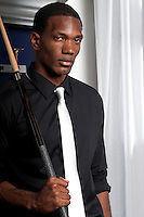 Young professional african american pool player posing with cue, in billiard saloon.