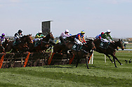 TheClockIsTicking ridden by Ciaran Gethings (14) and Vive Le Roi (19) ridden by Harry Bannister lead the way over the first hurdle in the1:45pm The Gaskells Handicap Hurdle (Grade 3) during the Grand National Meeting at Aintree, Liverpool, United Kingdom on 6 April 2019.
