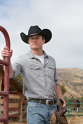 All American cowboy opening a gate on a ranch