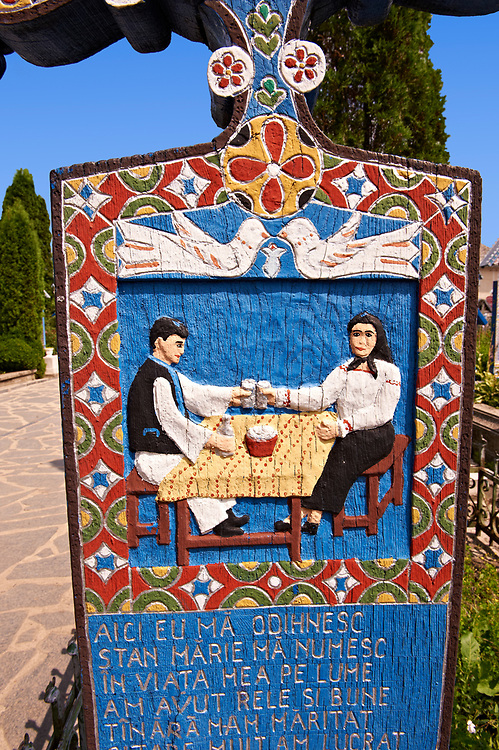 Tombstone of a Husband showing him drinking with his wife, The  Merry Cemetery ( Cimitirul Vesel ),  Săpânţa, Maramares, Northern Transylvania, Romania.  The naive folk art style of the tombstones created by woodcarver  Stan Ioan Pătraş (1909 - 1977) who created in his lifetime over 700 colourfully painted wooden tombstones with small relief portrait carvings of the deceased or with scenes depicting them at work or play or surprisingly showing the violent accident that killed them. Each tombstone has an inscription about the person, sometimes a light hearted  limerick in Romanian. .<br /> <br /> Visit our ROMANIA HISTORIC PLACXES PHOTO COLLECTIONS for more photos to download or buy as wall art prints https://funkystock.photoshelter.com/gallery-collection/Pictures-Images-of-Romania-Photos-of-Romanian-Historic-Landmark-Sites/C00001TITiQwAdS8