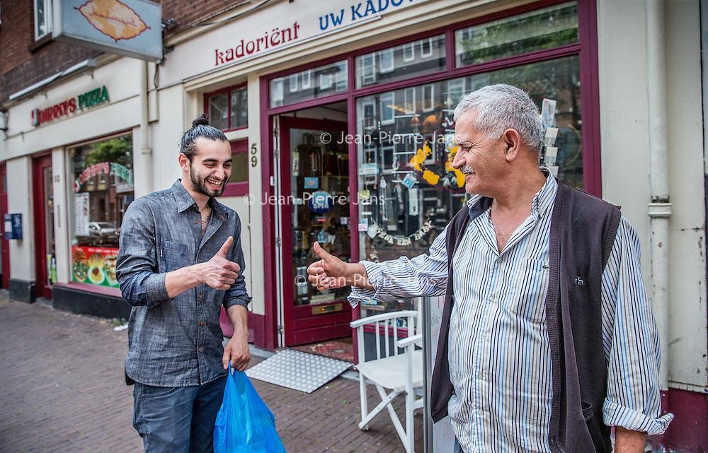 Nederland, Amsterdam, 23 juli 2016.<br />We volgen de Syrische jongen Ibrahim Najjar in de Spaarndammerbuurt in zijn zoektocht naar de ingredienten voor het Syrische kipgerecht Mskhan, een Syrisch ovengerecht met kip, citroen en ui.<br />Hij heeft zijn buren uitgenodigd bij hem te komen eten.<br />Op de foto: sfeerbeeld in de Spaarndammerstraat met Ibrahim en een Koerdische meneer.<br /><br /><br /><br />Foto: Jean-Pierre Jans
