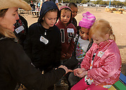 Kindergarteners from Rio Vista Elementary School visit the Tucson Village Farm, Tucson, University of Arizona, USA.  Elizabeth Sparks, (left), educates students about the benefits and life cycle of worms.