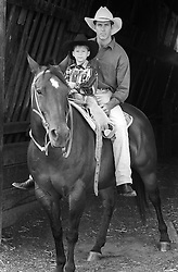 cowboy and small boy sitting on a horse together