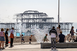 Licensed to London News Pictures. 06/09/2021. Brighton, UK. Kids chase bubbles on Brighton Beach, East Sussex as weather forecaster predict a mini-heatwave for September this week with temperatures hitting over 29c tomorrow. Photo credit: Alex Lentati/LNP