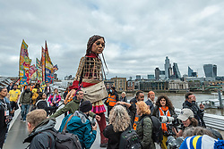© Licensed to London News Pictures. 23/10/2021. LONDON, UK.  Little Amal, a 3.5m tall living artwork, walks across the Millennium Bridge.  She is taking part in The Walk, produced by Good Chance Theatre, travelling 8,000km in support of refugees. Created by Handspring Puppet Company, Little Amal represents a young Syrian refugee child who walked from Turkey across Europe to the UK and her journey will end in Manchester in November.  Photo credit: Stephen Chung/LNP