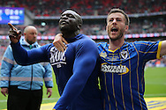 Adebayo Akinfenwa of AFC Wimbledon (l) celebrates after scoring his sides 2nd goal from a penalty with Jon Meades of AFC Wimbledon to make it 2-0. Skybet football league two play off final match, AFC Wimbledon v Plymouth Argyle at Wembley Stadium in London on Monday 30th May 2016.<br /> pic by John Patrick Fletcher, Andrew Orchard sports photography.