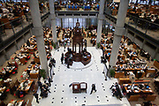 Brokers on the floor at Lloyds of London. The trading floor at Lloyds is the world's leading insurance market where It serves as a meeting place where multiple financial backers or 'members', whether individuals (traditionally known as 'Names' or corporations, come together to pool and spread risk. The modern building was designed by Sir Richard Rogers at Number One Lime Street in a Post-Modernist style.