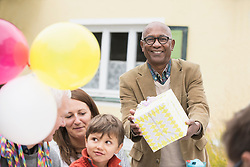 Black senior man giving birthday gift to his friend on his birthday, Bavaria, Germany