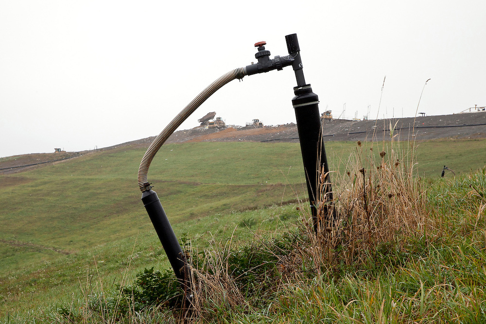 Methane gas pipe with valve coming up out of capped sanitary landfill