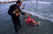 """Europe, France, Camargue, Saintes Maries de la Mer. Manouche Gypsy with violin holds his daughter who plays in the sea after Saint Sara's procession. The Gypsy festival """"le Pelerinage des Gitans aux Saintes Maries de la Mer"""" takes place every year in mid May. Gypsies arrive from all over Europe a few weeks before the main festival days, the 24th and 25th May.  The pilgrimmage is Catholic but many Gypsies, Manouche, Gitans, Roma come to see their patron 'Saint Sara' and for the festival atmosphere, the yearly gathering of friends, the music and dance. Gypsies are still regarded with much distrust and racism, they are not liked by the shopkeepers but are well treated by the gentry, especially the Baroncelli family who were instrumental in making this officially a Gypsy festival. One Hundred years ago the Gypsies were not allowed into the church, as it is they still have to camp outside the town."""
