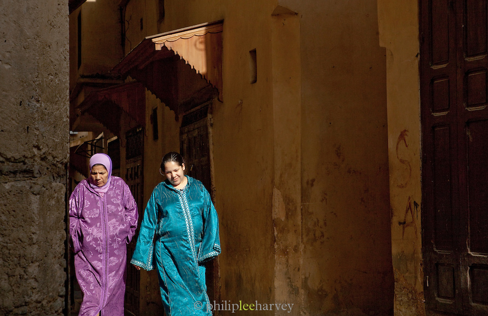 Two women walk in the narrow streets in the medina of Fes, Morocco