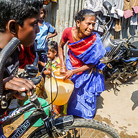 Weighing Heavily, Chennai, India by Kavya. <br /> <br /> A woman fetching water in an urban slum in Chennai, India.