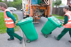 Binmen returning neighbourhood wheelie bins after unloading them into dust cart,